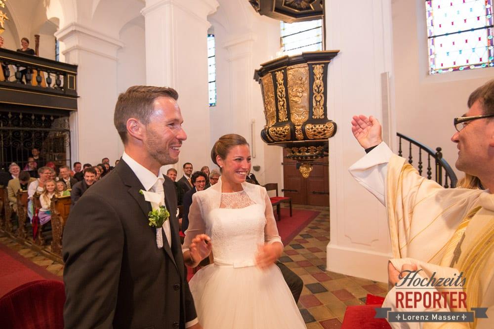 Brautpaar lacht den Pfarrer an bei Trauung, Schloss Mondsee, Hochzeit, Wedding, Wedding Photographer, Land Salzburg, Lorenz Masser