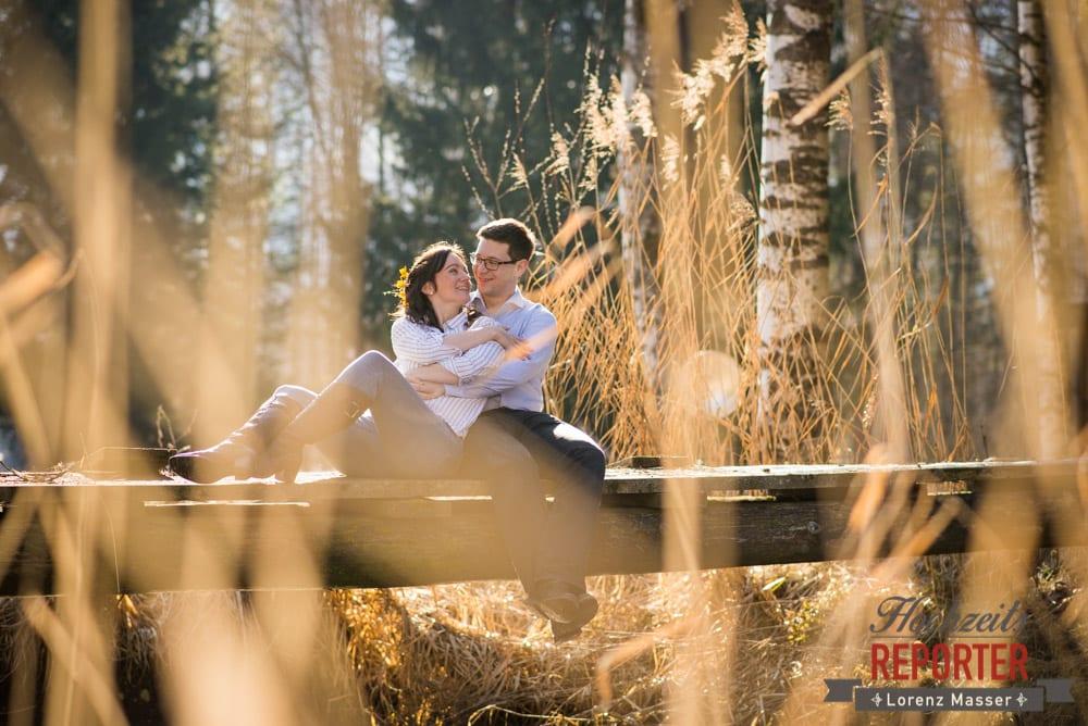 Verliebtes Paar sitzt auf Steg mit Sträuchern, Engagement Shooting, Schloss Prielau, Zell am See, Land Salzburg, Fotograf, Hochzeitsfotograf, Hochzeit, Lorenz Masser