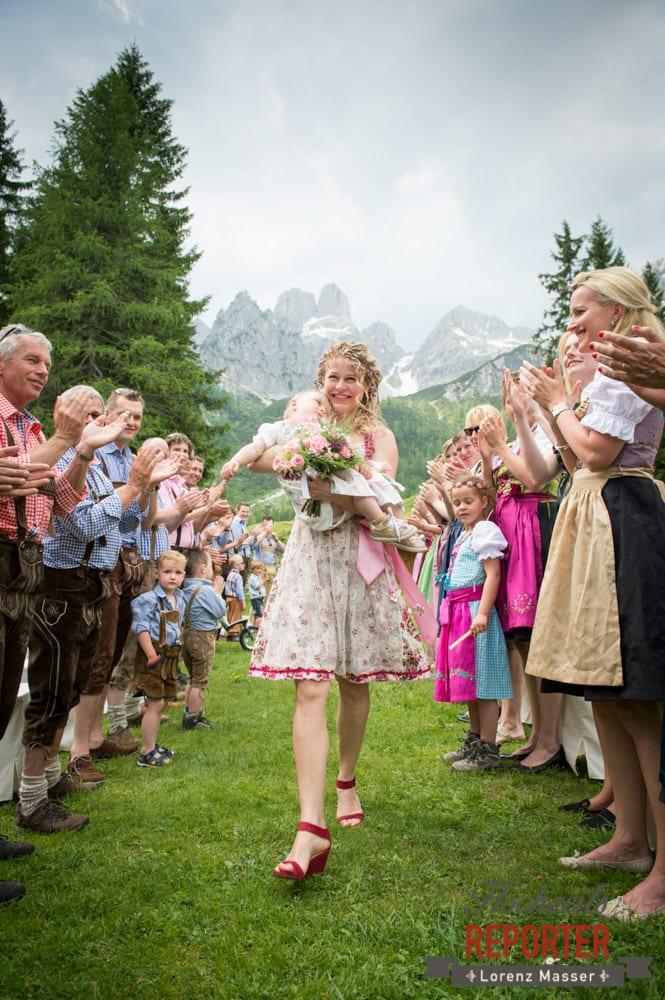 Braut geht mit Kind im Arm und wird Applaudiert,  Filzmoos, Hochzeitsfotograf, Wedding Photographer,Land Salzburg, Lorenz Masser