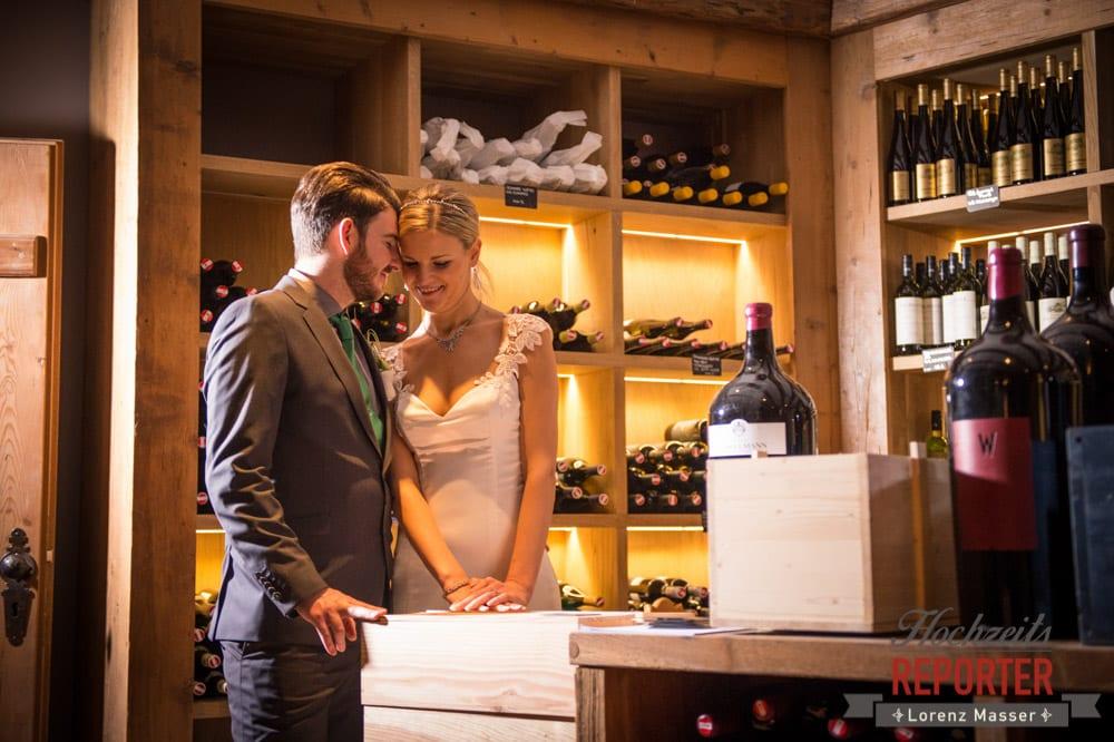 Brautpaar steht im Weinkeller und turtelt herum