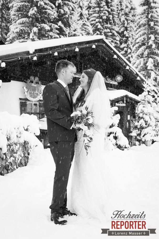 Brautpaar im Schnee, Brautpaar schaut sich an wenn es Schneit, Unterhofalm, Filzmoos, Winter Wedding, Hochzeit im Winter, Hochzeitsfotgraf, Lorenz Masser