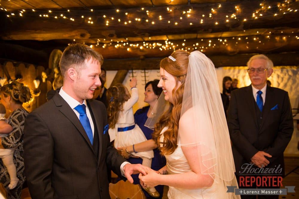 Brautpaar schaut sich während Ringwechsel in die Augen, Unterhofalm, Filzmoos, Winter Wedding, Hochzeit im Winter, Hochzeitsfotgraf, Lorenz Masser