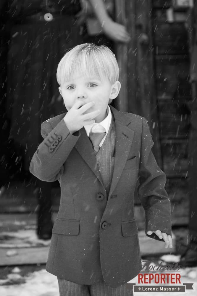 Kleiner Junge mit blonden Haaren im Anzug im Schnee, Unterhofalm, Filzmoos, Winter Wedding, Hochzeit im Winter, Hochzeitsfotgraf, Lorenz Masser