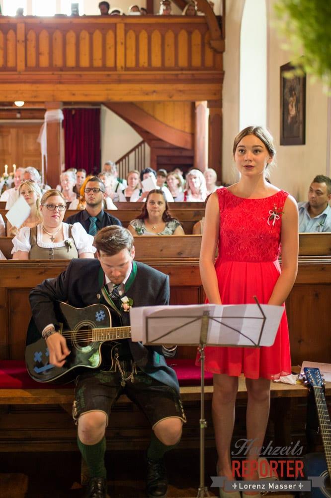 Gesang und Gitarrenmusik bei Trauung in Kirche, Frau in Rotem Kleid singt, Trauung in Kirche, Bad Aussee, Hochzeitsfotograf, Land Salzburg, Lorenz Masser