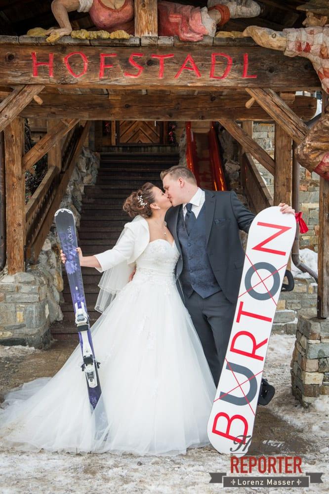 Brautpaar im Hofstadl, Brautpaar mit Ski und Snowboard, Kuss, Hofstadl in Flachau, Fotograf Land Salzburg