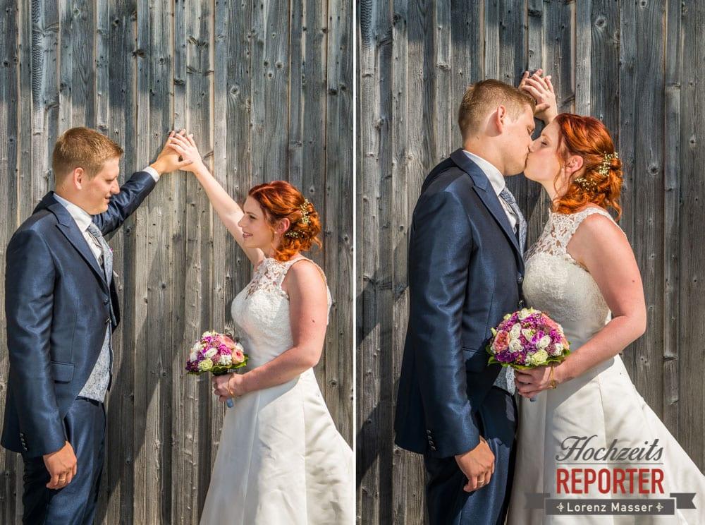 Brautpaar küsst sich vor Holzwand, Lisa Alm, Hochzeit, Wedding, Hochzeitsfotograf, Land Salzburg, Lorenz Masser